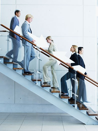 Male and female office workers on staircase holding arrow signs : Stock Photo