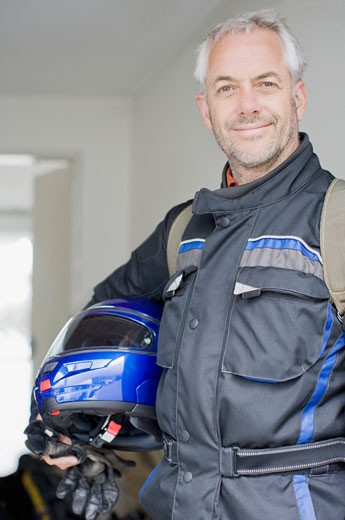 Man in coverall holding helmet and gloves : Stock Photo