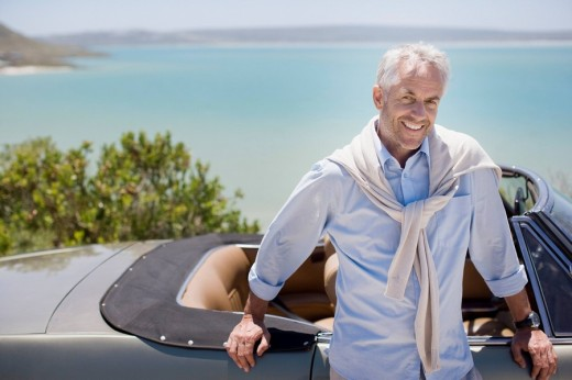 Man leaning on convertible at waterfront : Stock Photo