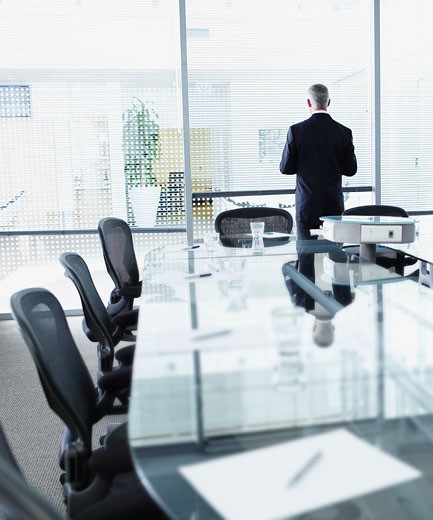 Businessman alone in a boardroom facing window : Stock Photo
