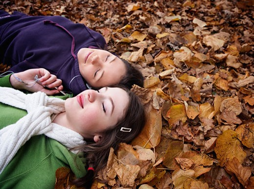 Teenage girls laying in leaves listening to mp3 player : Stock Photo