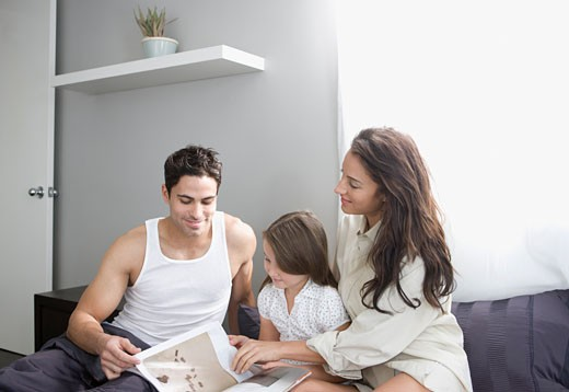 Stock Photo: 1775R-14971 Family reading story in bed together
