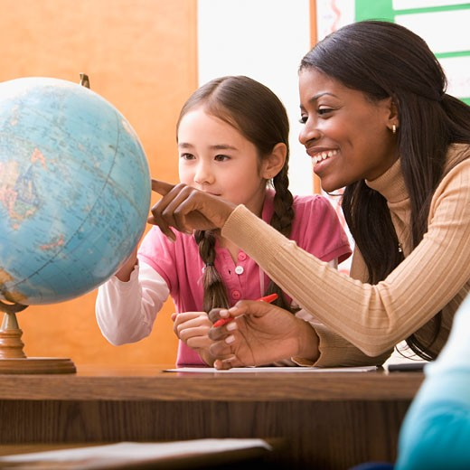 Teacher and student looking at globe : Stock Photo
