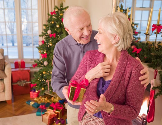 Man surprising woman with Christmas gift : Stock Photo