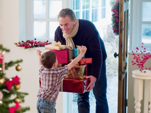 Boy running to father holding Christmas gifts in doorway : Stock Photo