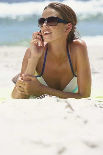 Stock Photo: 1775R-1531 Woman with sunglasses lying down at beach with cell phone