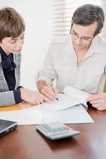 Businesswoman guiding man with paperwork : Stock Photo