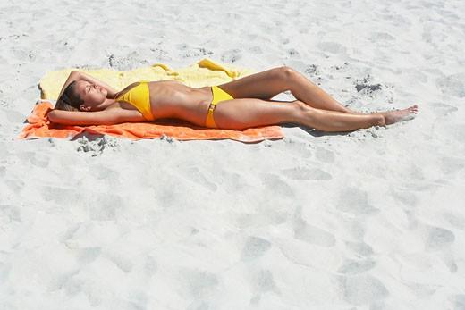 Stock Photo: 1775R-1538 Woman lying down on beach towel sunbathing