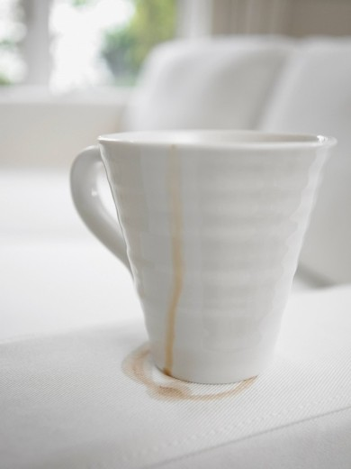 Stock Photo: 1775R-15484 Close up of coffee cup making stain on sofa