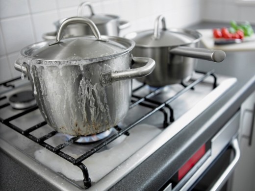Pot boiling over in kitchen : Stock Photo