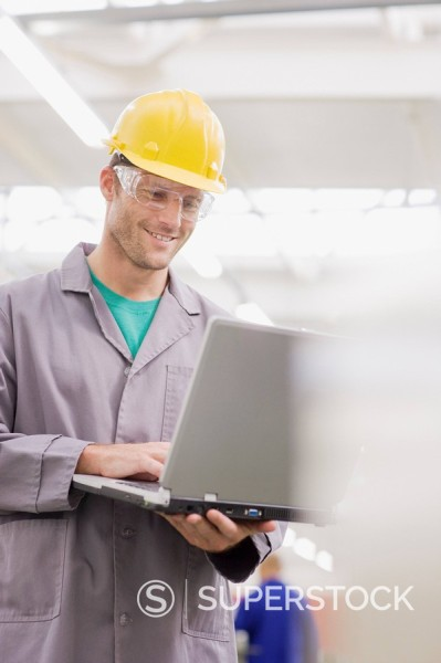 Worker in coveralls, hard_hat and safety goggles using laptop : Stock Photo