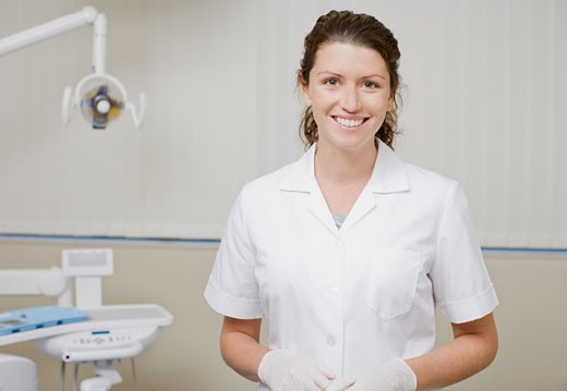 Dental hygienist standing in dentist's examination room : Stock Photo