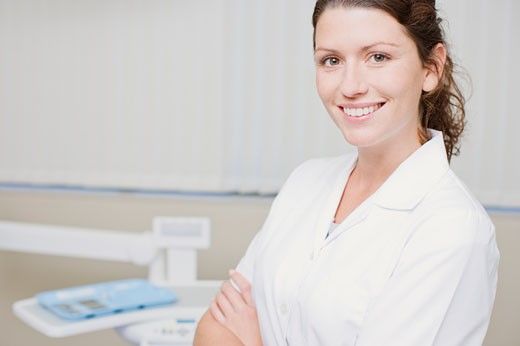 Stock Photo: 1775R-15701 Dental hygienist standing in dentist's examination room