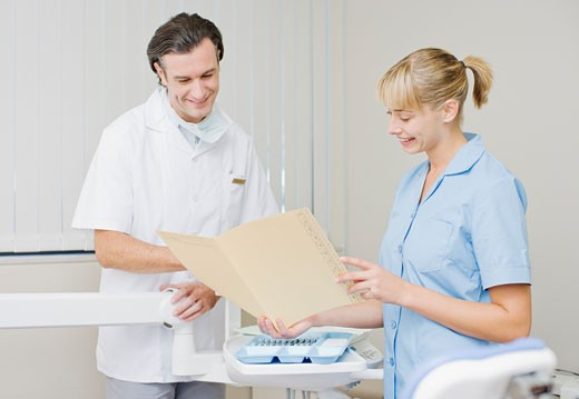 Dentist and dental hygienist reviewing records in dentist's examination room : Stock Photo