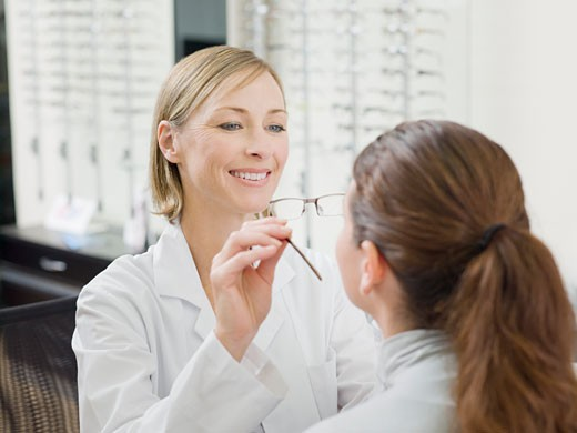 Woman trying on glasses in optometrist's shop : Stock Photo