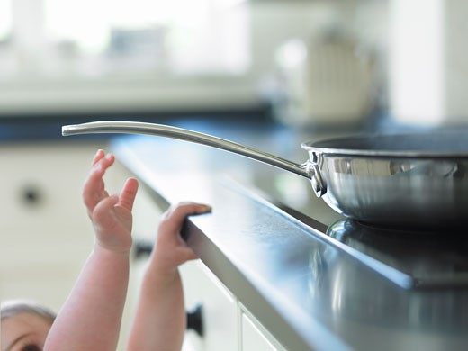 Baby reaching for hot frying pan on stove : Stock Photo