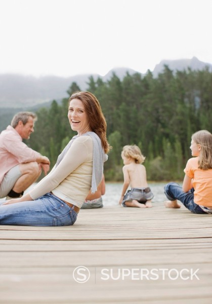 Family sitting on pier by lake : Stock Photo