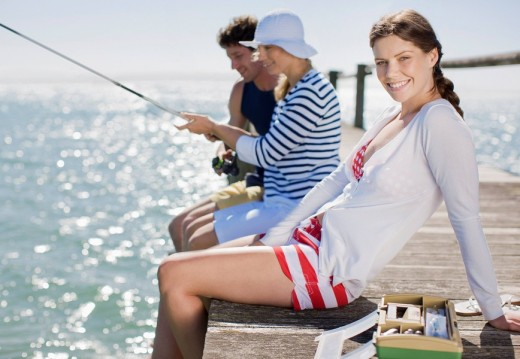 Friends fishing off pier at ocean : Stock Photo