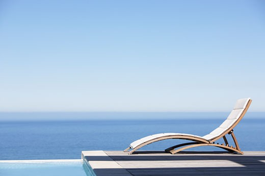 Folding chair on infinity pool deck : Stock Photo
