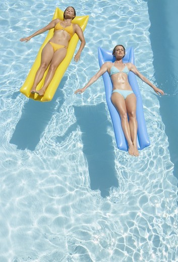 Stock Photo: 1775R-1637 Two women on flotation devices in pool