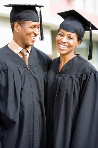 Graduates in caps and gowns smiling : Stock Photo