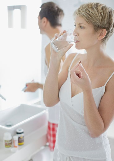 Woman taking vitamins in the morning : Stock Photo