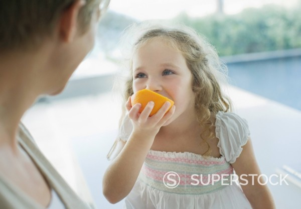 Stock Photo: 1775R-16580 Mother watching girl eating orange