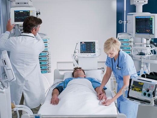 Doctor and nurse attending patient in intensive care : Stock Photo