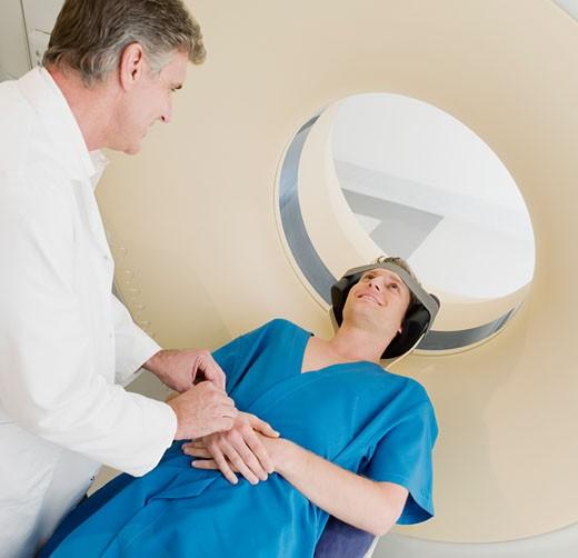 Technician preparing patient for MRI examination : Stock Photo
