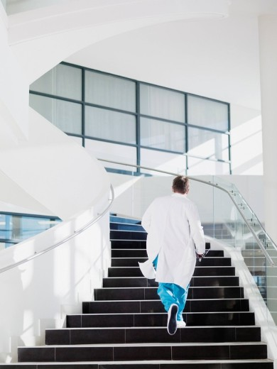 Doctor running up hospital staircase : Stock Photo