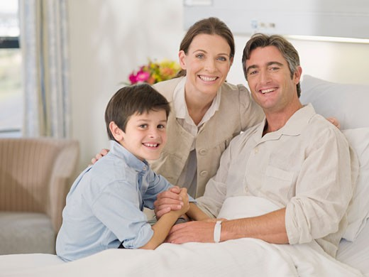 Stock Photo: 1775R-16846 Wife and son visiting recovering husband in hospital