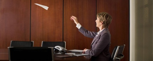 Businesswoman throwing paper airplane : Stock Photo