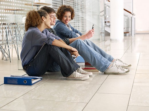 Friends sitting on floor and looking at cell phone : Stock Photo