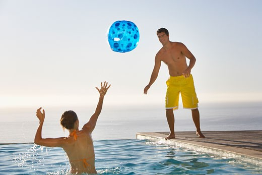 Man and woman playing with beach ball in infinity pool : Stock Photo