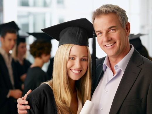 Father and graduate daughter hugging : Stock Photo
