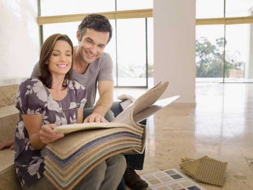 Couple looking at carpet samples in empty house : Stock Photo