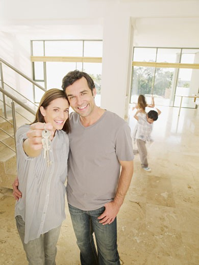 Happy couple holding keys in new house : Stock Photo