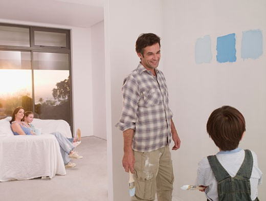 Father and son looking at paint samples on wall : Stock Photo