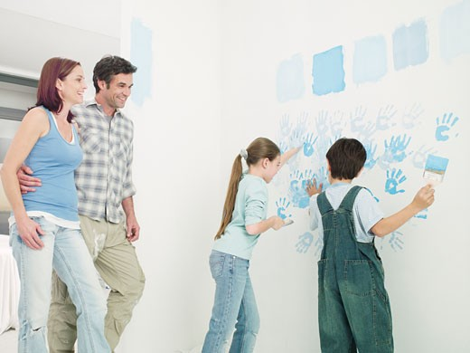 Stock Photo: 1775R-17121 Parents watching kids paint handprints on wall