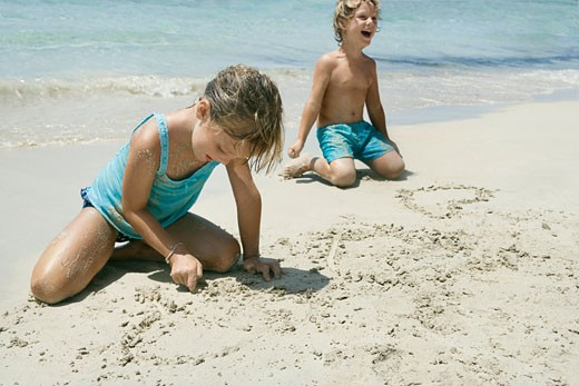Boy and girl writing in sand on beach : Stock Photo