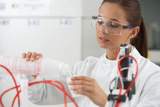 Stock Photo: 1775R-17268 Scientist pouring liquid into cup in laboratory