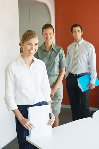 Three businesspeople standing in office with documents : Stock Photo