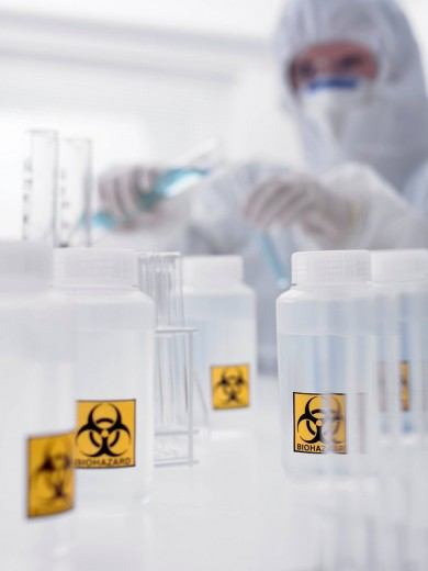 Scientist and bottles with biohazard labels : Stock Photo