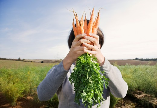 Woman hiding face behind carrots : Stock Photo