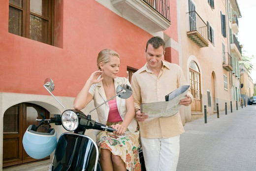 Man and woman with scooter reading map : Stock Photo