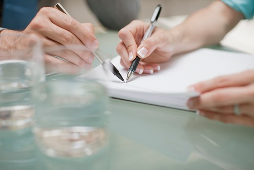 Stock Photo: 1775R-18136 Business people pointing at paperwork with pens