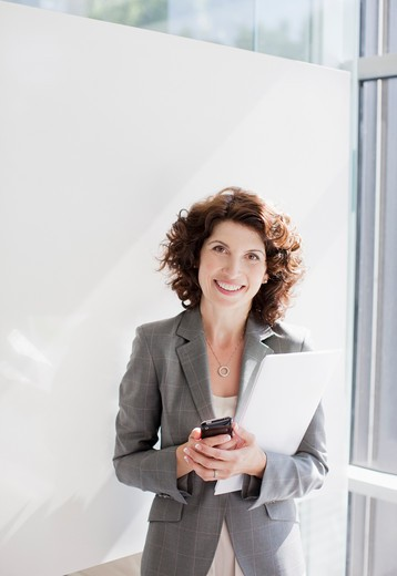 Businesswoman holding file and cell phone : Stock Photo