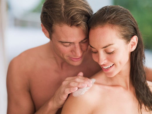 Man applying lotion to woman's shoulder : Stock Photo