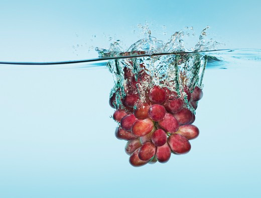 Stock Photo: 1775R-18546 Bunch of red grapes splashing in water