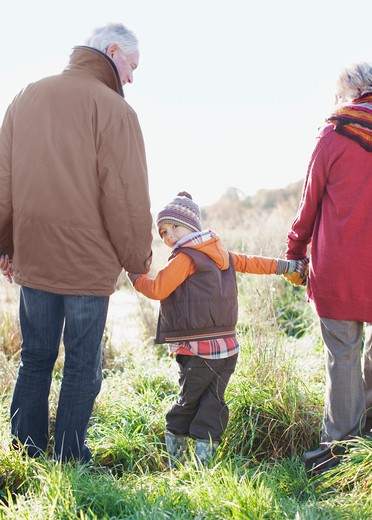Grandparents holding hands with grandson : Stock Photo